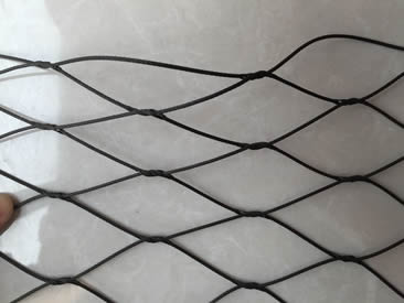 A piece of black knotted rope mesh is on the floor.