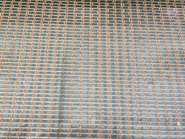 A piece of rectangular laminated glass metal mesh with copper cable mesh inter-layer.