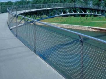 Bridge balustrade made of architectural rope mesh and under the bridge there is a river.