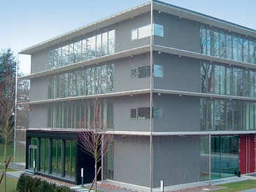 A building is covered with architectural rope mesh and near the building there are two trees.