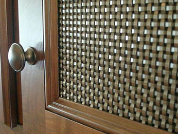 A cabinetry screen with a wooden frame and a handle is made of bronze woven screen.