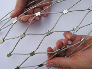 Two hands are holding two ends of the architectural rope mesh.