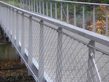 Bridge balustrade made of silver white architectural rope mesh in garden.