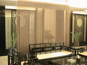 Woven wire mesh used as space divider and beside the mesh there are antique furniture.