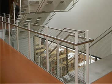 A corner of stair balustrade is made of architectural rope mesh.