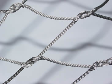 A section of rope mesh made of thick rope with four knots.