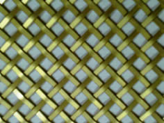Architectural woven mesh made of flat brass wire.